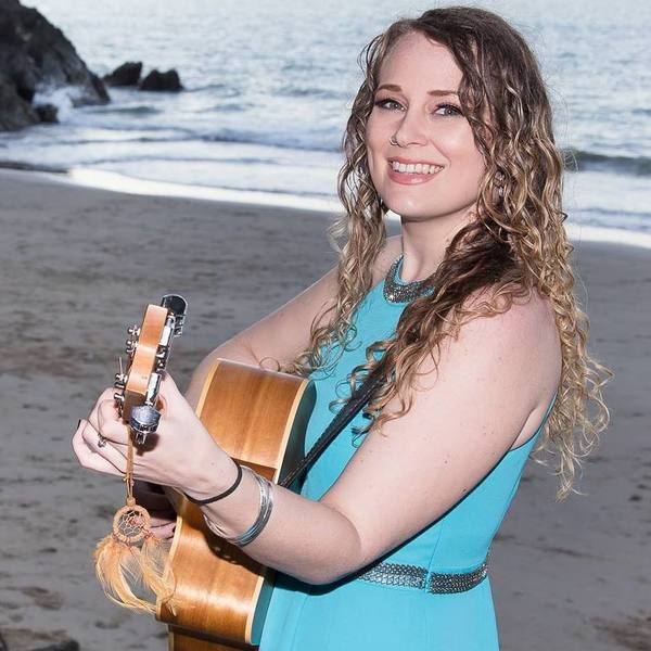Talitha Power, playing a guitar at the beach.
