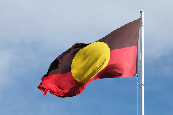 Aboriginal flag against a blue sky with clouds
