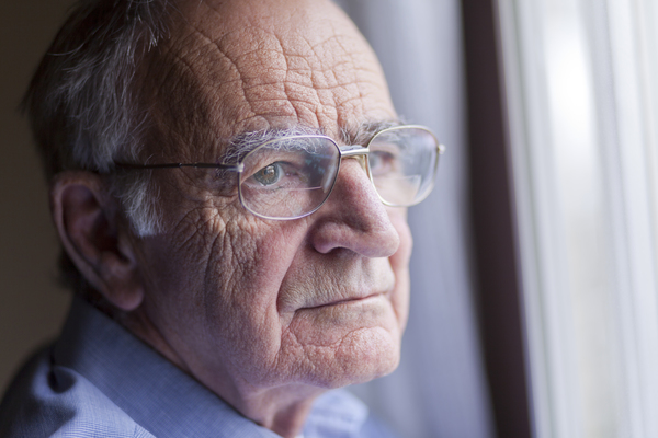 Older white man with glasses gazing into the distance